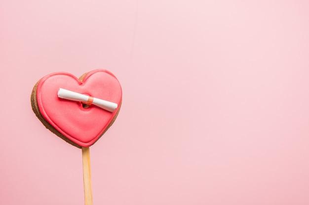 Czerwone ciasteczko w kształcie serca z listem miłosnym na różowej, walentynkowej kartce z życzeniami.