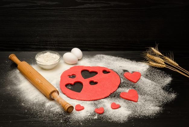 Czerwone ciasto, wyciąć serca, mąkę, jajka i wałek do ciasta na czarny, kłosy pszenicy, copyspace