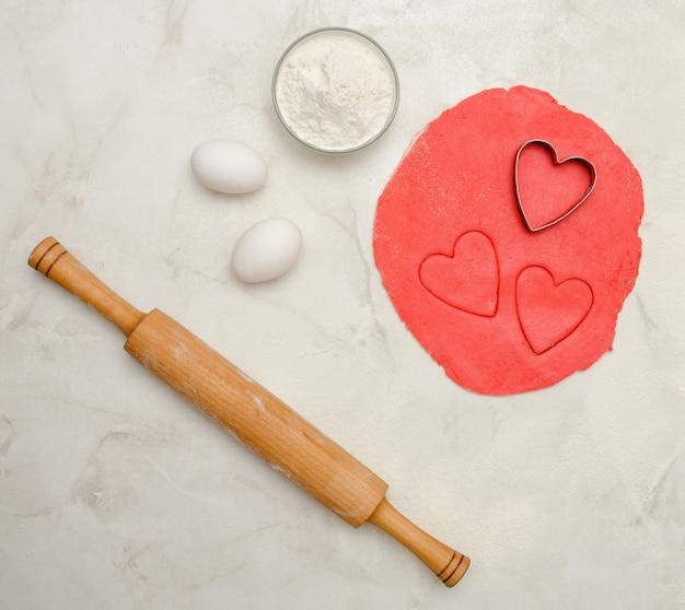 Czerwone ciasto z wyciętym sercem, jajkami, mąką i wałkiem do ciasta, na białym stole. widok z góry, miejsce na tekst