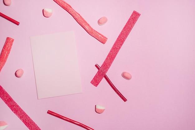 Czerwone cukierki i lizaki z pustej kartki papieru
