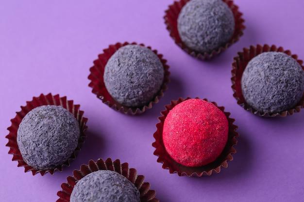 Czerwone cukierki wśród fioletowych w kolorze. pojęcie wyjątkowości