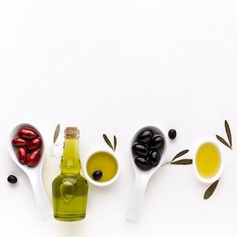 Czerwone czarne oliwki w łyżkach z butelką oleju