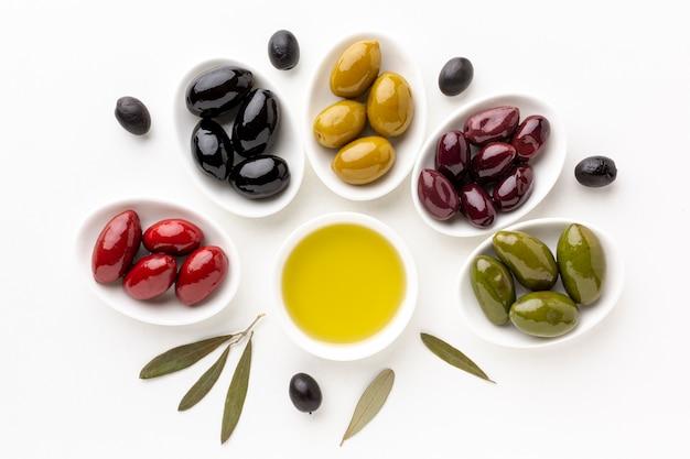Czerwone czarne żółte fioletowe oliwki na talerzach z liśćmi i spodkiem z oliwek