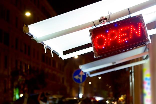Czerwone diody led otwarty znak w nocy na ulicy.