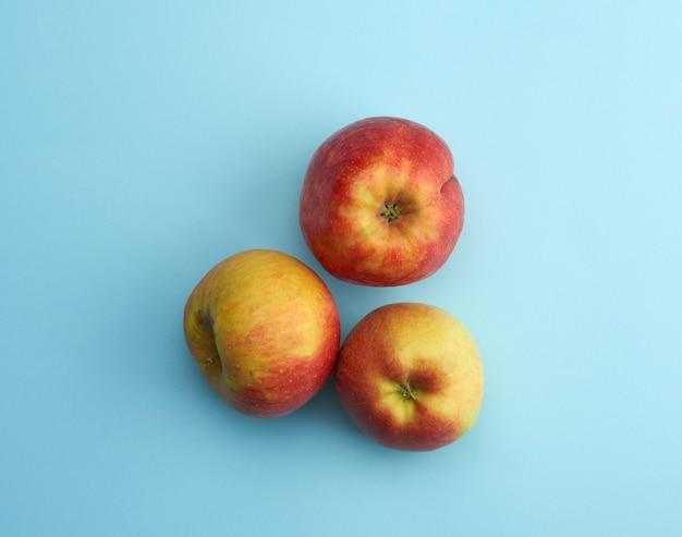 Czerwone dojrzałe jabłka okrągłe na białym tle na niebiesko