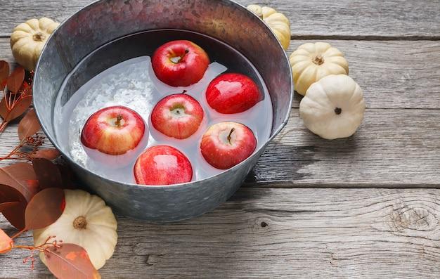 Czerwone dojrzałe jabłka pływające w czystej wodzie w metalowej misce, małe dynie i suche liście opadają martwą naturą. kompozycja owoców i warzyw na rustykalnym drewnie
