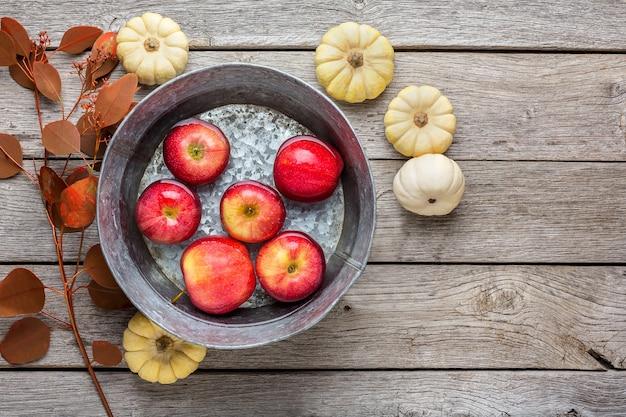 Czerwone dojrzałe jabłka w czystej wodzie w metalowej misce, małe dynie i suche liście opadają martwą naturą. kompozycja owoców i warzyw na rustykalnym drewnie, widok z góry