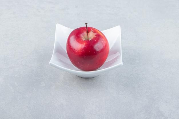Czerwone dojrzałe jabłko w białej misce.