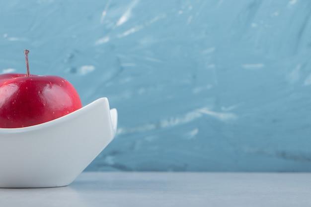 Czerwone dojrzałe jabłko w białej misce
