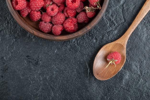 Czerwone dojrzałe maliny w drewnianej misce na marmurowym stole