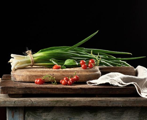 Czerwone dojrzałe pomidory czereśniowe i wiązka zielonej cebuli