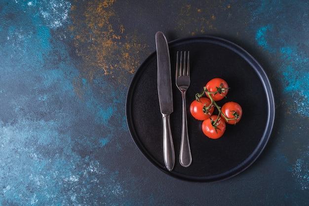 Czerwone dojrzałe pomidory i sztućce na talerzu.