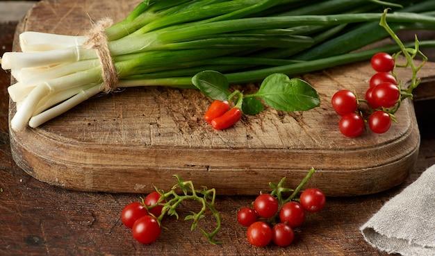 Czerwone dojrzałe pomidory koktajlowe i wiązka zielonej cebuli związane liną