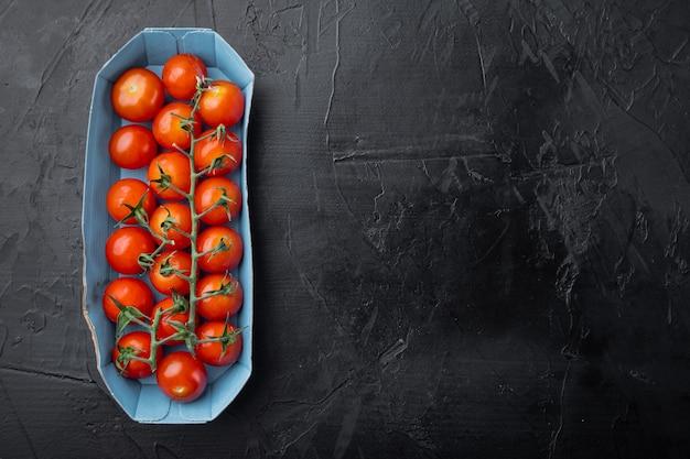 Czerwone dojrzałe pomidory koktajlowe, na czarnym tle z miejscem na tekst