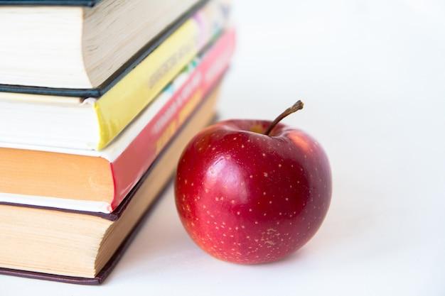 Czerwone dojrzałe, soczyste jabłko w pobliżu książek