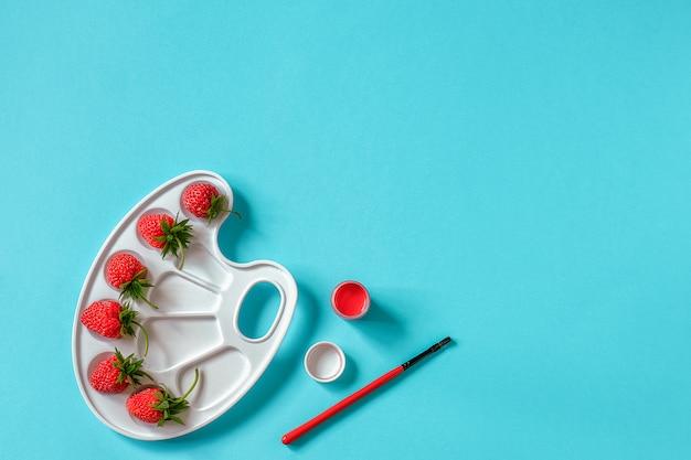 Czerwone dojrzałe truskawki na artystycznej palecie, muśnięciu i guaszie na błękicie z kopii przestrzenią