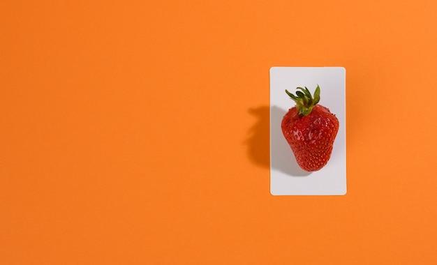 Czerwone dojrzałe truskawki na pomarańczowej powierzchni, płaskie ay