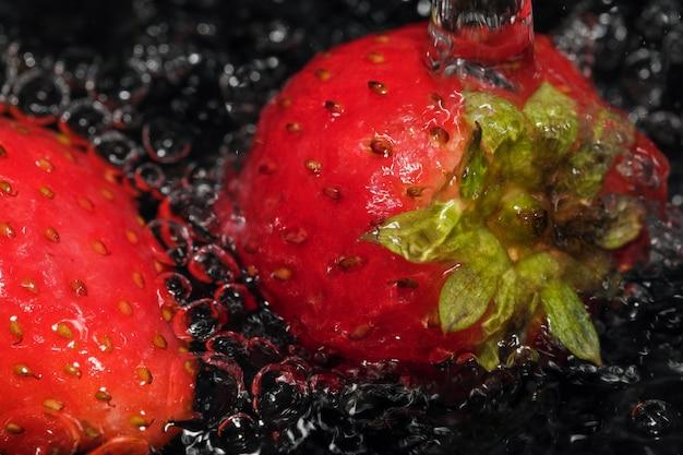 Czerwone dojrzałe truskawki są myte w czystej wodzie makrofotografii z bliska na czarnym tle