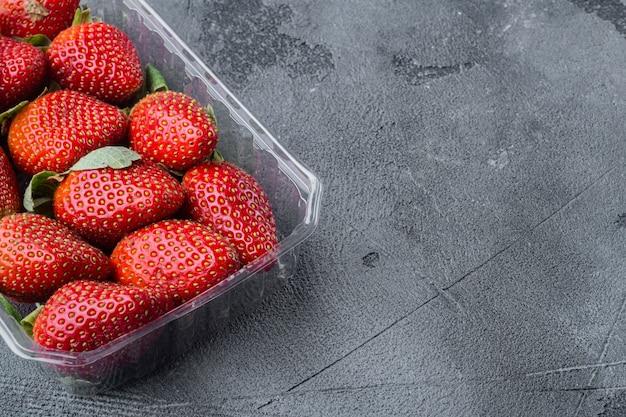 Czerwone dojrzałe truskawki w przezroczystej plastikowej tacy, na szarym tle z miejscem na tekst