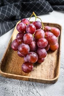 Czerwone dojrzałe winogrona w drewnianej misce