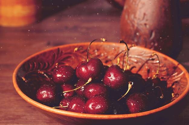 Czerwone dojrzałe wiśnie leżą na brązowym talerzu obok brązowego dzbanka na stole w wiosce