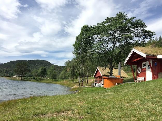 Czerwone, drewniane domy z trawiastym dachem w stylu skandynawskim nad jeziorem