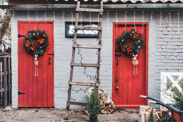 Czerwone drewniane drzwi na podwórku ozdobione świątecznym wieńcem.
