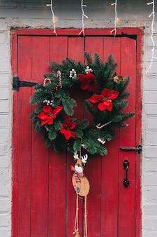 Czerwone drewniane drzwi ozdobione świątecznym wieńcem.