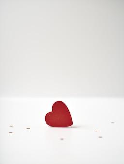 Czerwone drewniane serce i małe złote gwiazdki na jasnym tle. koncepcja walentynki.