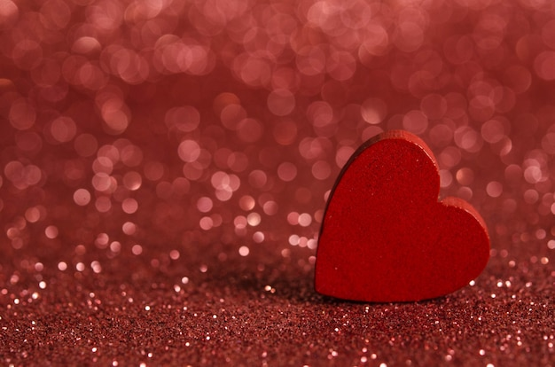 Czerwone drewniane serce na błyszczącej powierzchni