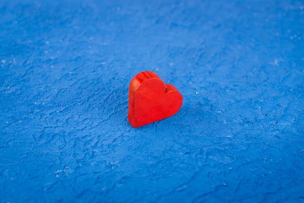 Czerwone drewniane serce na niebieskim tle z teksturą. pojęcie miłości i romansu z miejsca na tekst. otwórz na walentynki tapety na pulpit.
