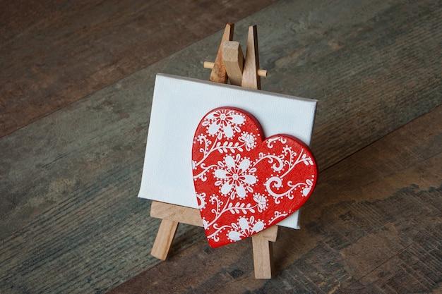 Czerwone drewniane serce z namalowanym wzorem stoi na małym trójnogu z czystym białym płótnem