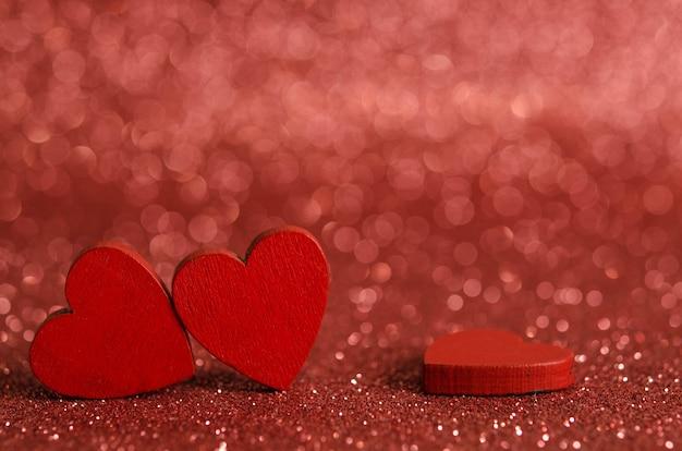 Czerwone drewniane serduszka na błyszczącej powierzchni