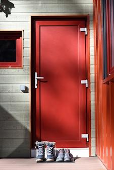 Czerwone drzwi z butami na drzwiach w zimowej chacie