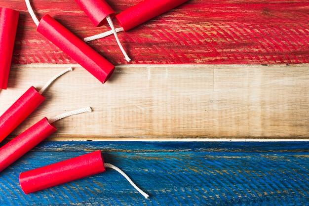 Czerwone dynamitowe petardy na drewnianym malującym drewnianym deski tle