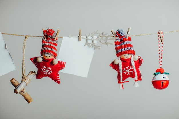 Czerwone dzianiny gwiazd w śmieszne czapki. świąteczne lalki i ozdoby wiszące na sznurze z spinaczem do bielizny. biały kawałek papieru na tekst.