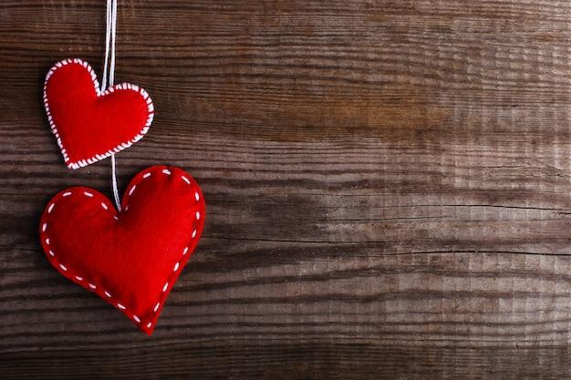 Czerwone filcowe serca na drewnianym stole. ręcznie wykonane puste karty, miejsce.