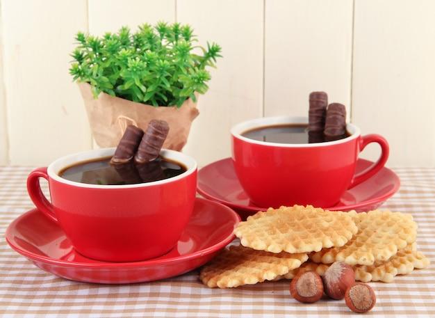 Czerwone filiżanki mocnej kawy z tabliczkami czekolady i goframi na obrusie na drewnianym