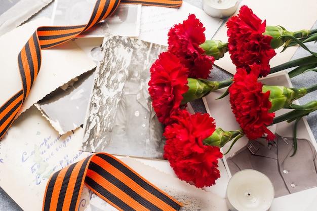 Czerwone goździki george ribbon stare zdjęcia na betonowym tle.