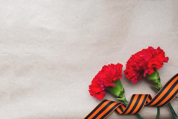 Czerwone goździki i wstążka św. jerzego na starym tle papieru.