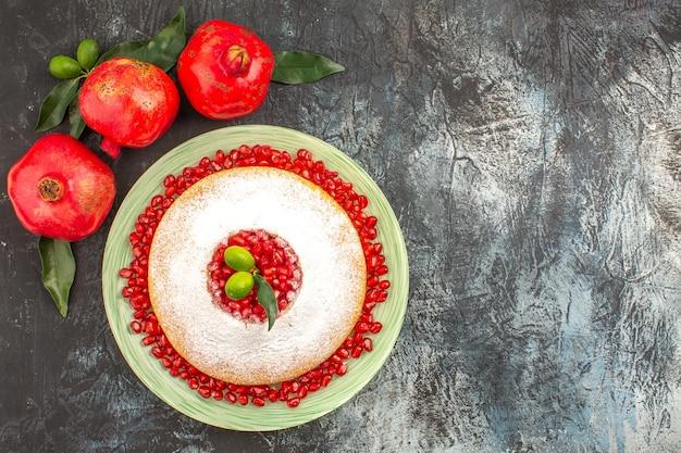 Czerwone granaty trzy granaty z listkami obok apetycznego ciasta