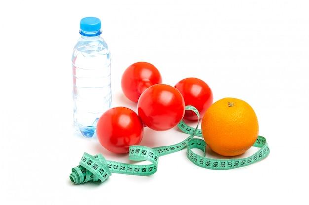 Czerwone hantle, świeży pomarańczowy, miarka lub miarka i naturalna butelka wody gazowanej na białym tle. pojęcie zdrowego stylu życia, fitness, diety