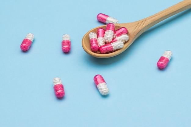 Czerwone i białe kapsułki z lekiem w drewnianej łyżce na niebieskiej powierzchni