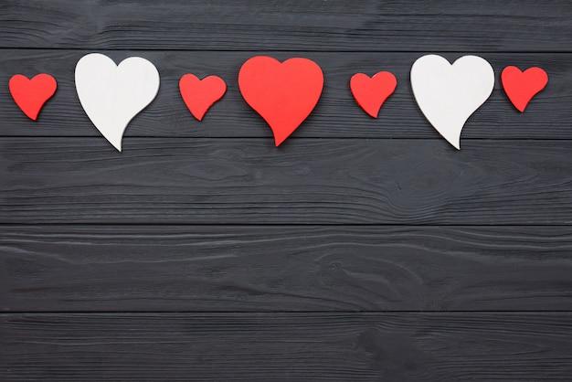 Czerwone i białe serca na ciemnej powierzchni drewnianej