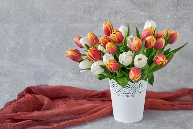 Czerwone i białe tulipany w białym wazonie. tło wakacje, miejsce na kopię