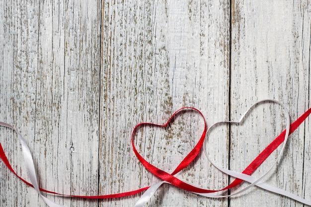Czerwone i białe wstążki serca na walentynki na podłoże drewniane