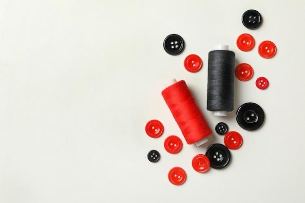 Czerwone i czarne wątki i przyciski na białym tle
