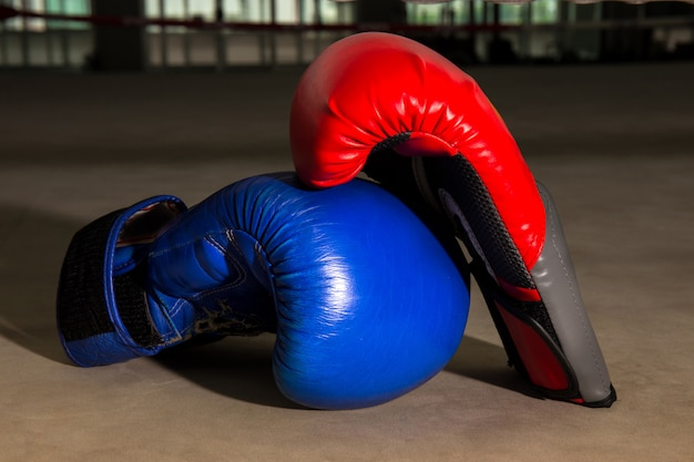 Czerwone i niebieskie rękawice bokserskie na ringu bokserskim w siłowni