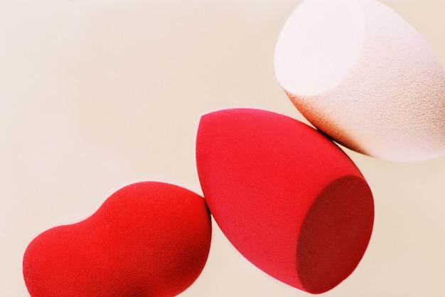 Czerwone i różowe gąbki kosmetyczne z bliska puff do makijażu do kremu tonizującego