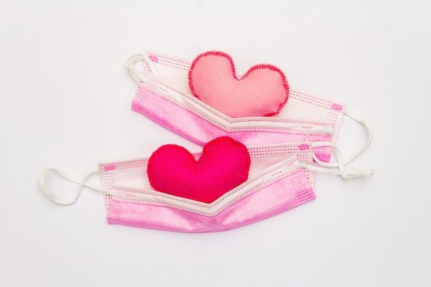 Czerwone i różowe serca z maskami ochrony medycznej na białym tle, widok z góry, miejsce. koncepcja opieki zdrowotnej, samoobrony, płaska świecka